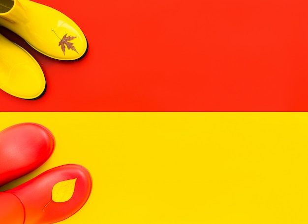 Red rubber boots to stand on a yellow background Premium Photo