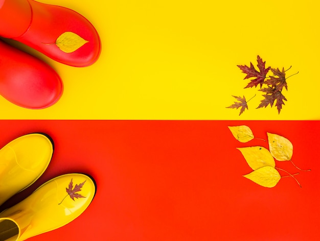 Red rubber boots stand on yellow and the yellow boots are on red. Premium Photo