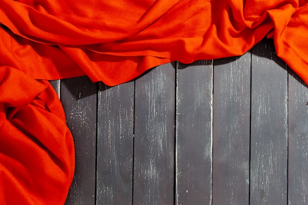 Red scarf over black wood table Premium Photo