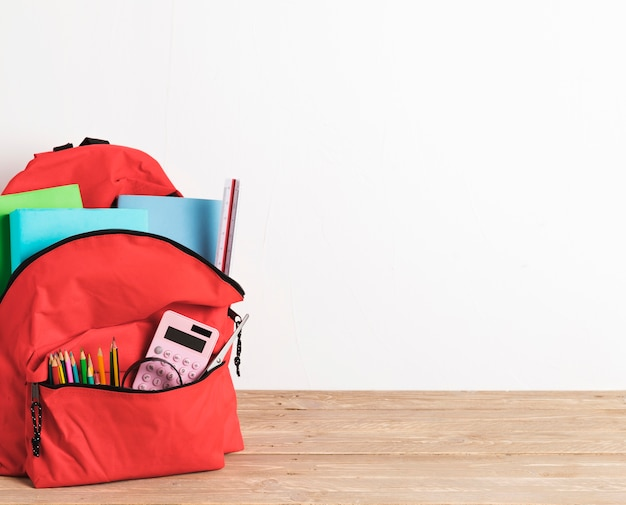 Red school bag with essential supplies Free Photo