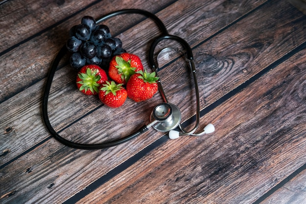 Fragole rosse scozzesi e uva nera con lo stetoscopio sulla parte superiore del tavolo in legno. cibo sano e medico concettuale. Foto Gratuite
