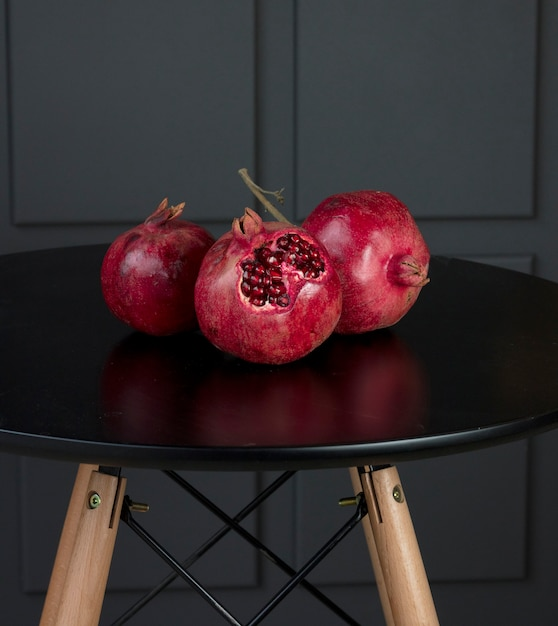 Red seasonal big pomegranates on a black table with wooden stands Free Photo
