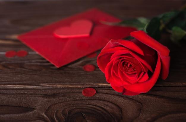 Красная форма сердца и красная роза на деревянном коричневом фоне Premium Фотографии