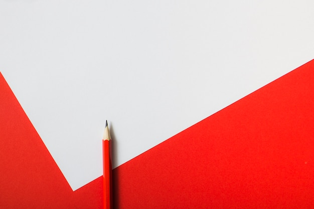 Red sharp pencil on dual white and red paper background Free Photo
