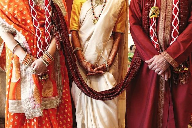 Красный платок соединяет родителей невесты, одетых для индийской свадьбы Бесплатные Фотографии