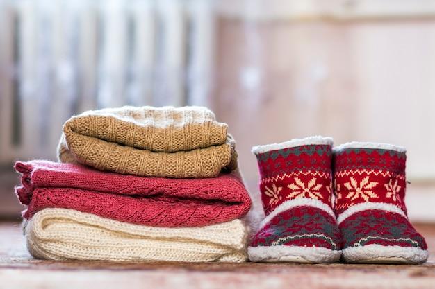 新年のパターンとニットセーターの山と赤い靴 Premium写真