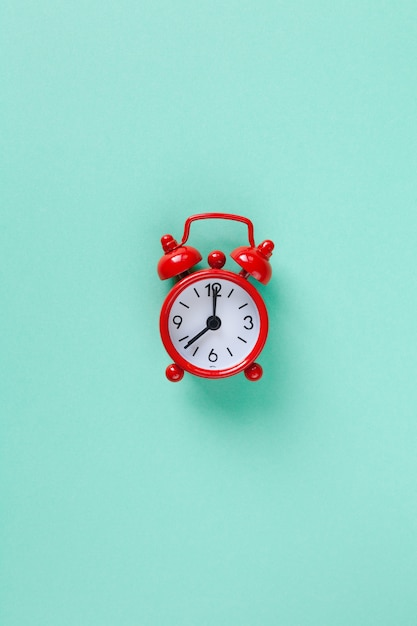 Red small alarm clock on pastel turquoise background with copyspace. Premium Photo
