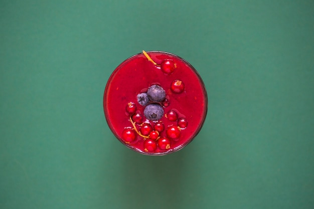 Red smoothie with berries in glass on green background Free Photo