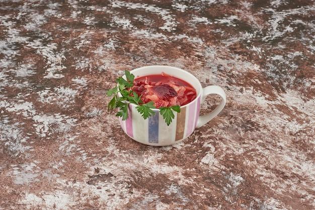 白いカップにハーブを添えた赤いスープ。 無料写真