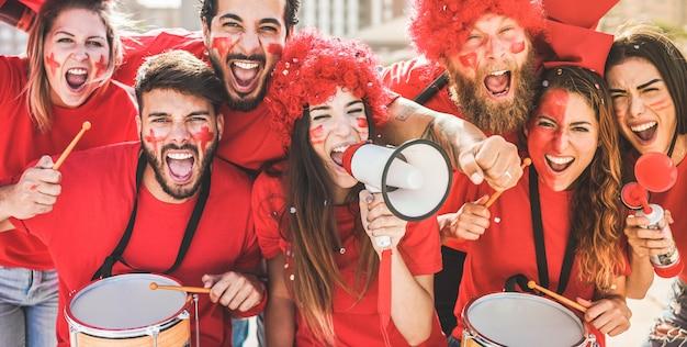 Красные фанаты спорта кричат, поддерживая свою команду со стадиона Premium Фотографии
