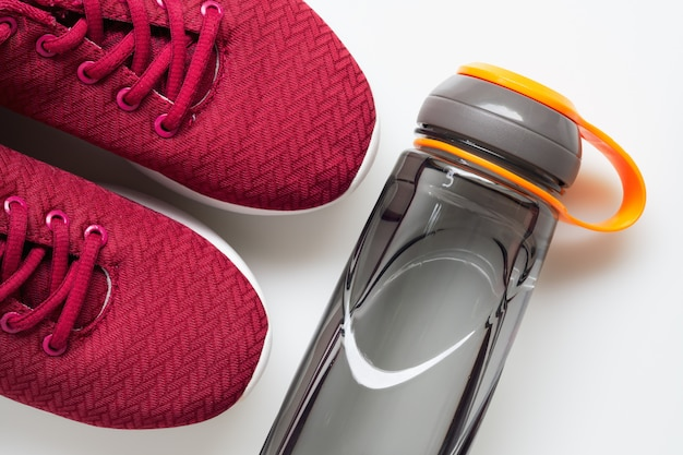 Red sport shoes and bottle of water. active healthy lifestyle background. Premium Photo