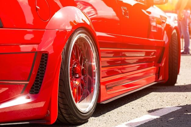 ホイールの赤いスポーツチューンドカーリアビュー、クローズアップ。道路上のファッションカーの日 無料写真