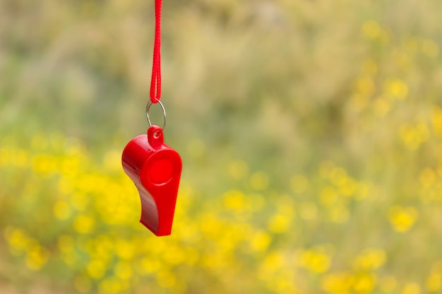 Red sports whistle on a background of yellow flowers. Premium Photo