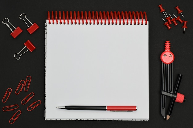 Red stationery items and blank spiral notebook on a black background. stationery set. geometric drawing compass, paper clips, stationery pin around white paper notebook with pen. Premium Photo