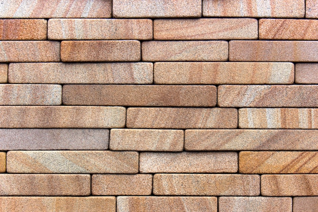 砂岩のタイルで飾られた赤い石の壁。背景またはテクスチャ Premium写真