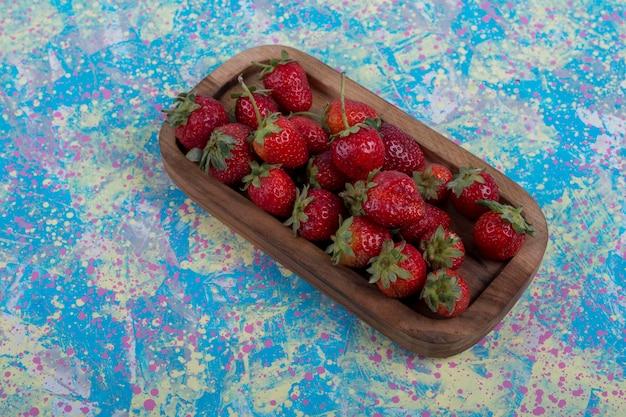 Красная клубника в деревянном блюде на синем фоне Бесплатные Фотографии
