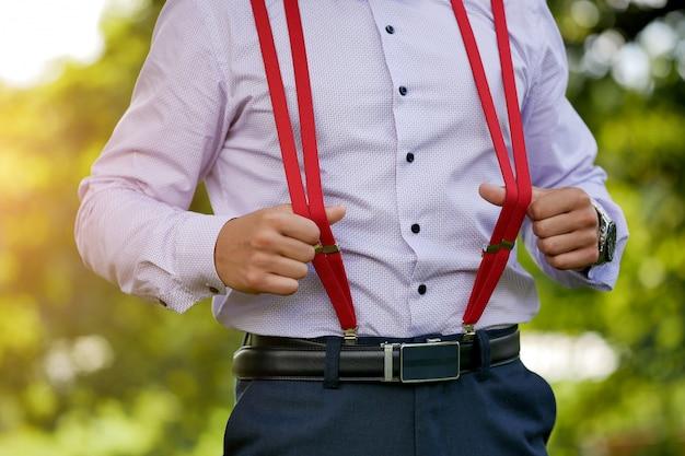Red stylish men's suspenders on blue shirt Premium Photo