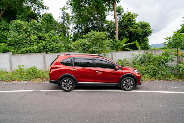 Red suv car on asphalt road with mountain green forest transportation to travel concept Premium Photo