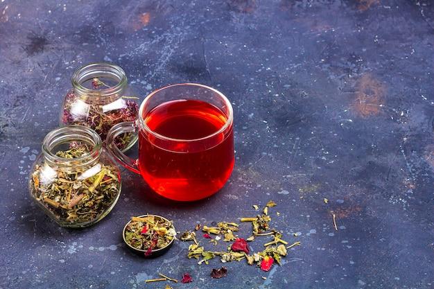 ガラスのカップと乾燥茶葉と花びらの瓶に赤茶 Premium写真