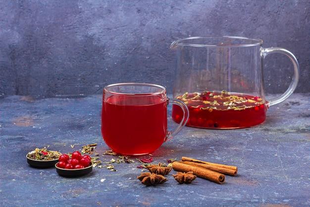 ガラスのカップとシナモン、アニス、クランベリーの暗闇の中のティーポットの赤茶 Premium写真