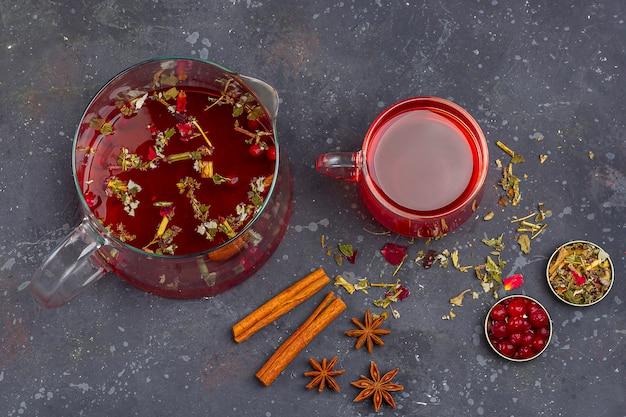 乾燥茶葉と花びらの中でガラスカップとティーポットの赤茶 Premium写真