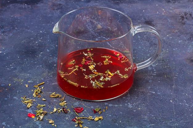 乾燥した茶葉と暗い背景に花びらとガラスのティーポットの赤茶。風邪やインフルエンザのためのハーブ、ビタミン、デトックスティー。 Premium写真