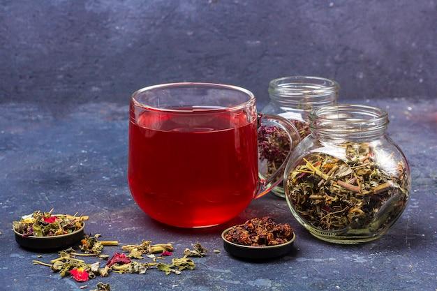 ガラスのカップと乾燥茶葉と暗い背景に花びらの瓶に赤茶(ルイボス、ハイビスカス、カルカデ)。風邪やインフルエンザのためのハーブ、ビタミン、デトックスティー Premium写真