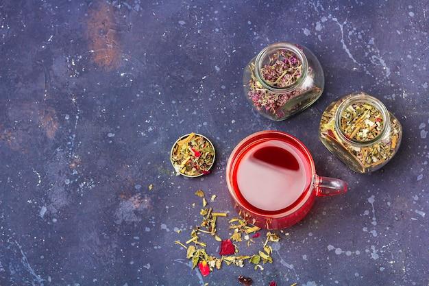 ガラスのカップと乾燥茶葉と暗い背景に花びらの瓶に赤茶(ルイボス、ハイビスカス、カルカデ) Premium写真