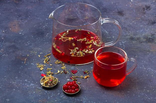乾燥茶葉、花びら、暗い背景上のクランベリーの中でガラスカップとティーポットの赤茶(ルイボス、ハイビスカス、カルカデ)。風邪やインフルエンザのためのハーブ、ビタミン、デトックスティー Premium写真