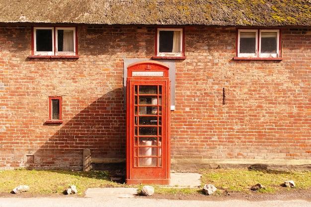 Красная телефонная будка у кирпичной стены с окнами Бесплатные Фотографии