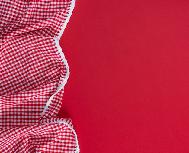 Red textile towel in a white cell on a red background Premium Photo