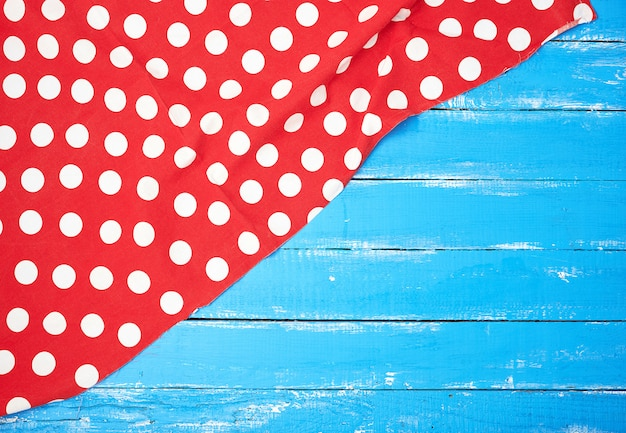 Red textile towel with white circles on a blue wooden background Premium Photo