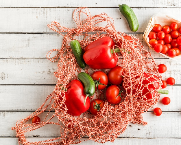 Red tomatoes and bell peppers, cucumbers in a string bag on white rustic background Premium Photo