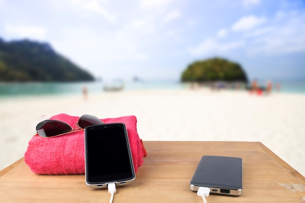 Red tower, sun glasses, mobile charging with power bank over wooden table on blur beach sand and blue sky background. Free Photo