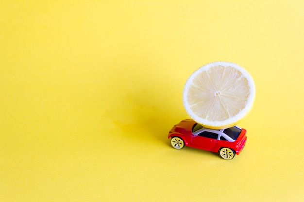 Red toy car lucky with fresh lemon, citrus delivery Premium Photo