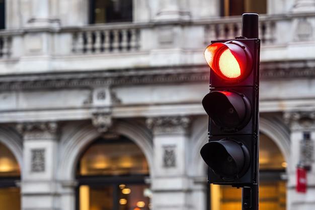ぼやけた建物の車の赤信号 Premium写真