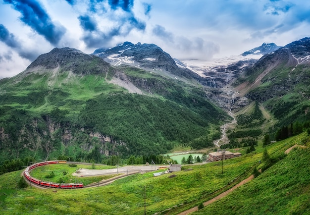 Red train bernina express to the passage in the mountains. Premium Photo