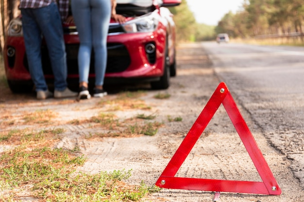 Red triangle sign on the road for car problems while traveling Free Photo