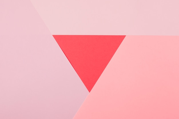 Red triangle surrounded with pink paper background Free Photo