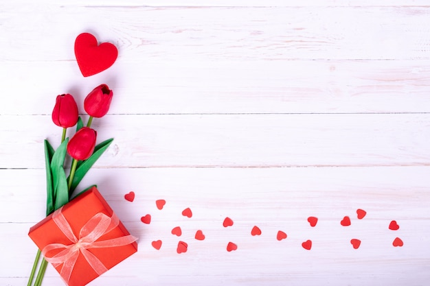 Red tulips bouquet and a gift Premium Photo