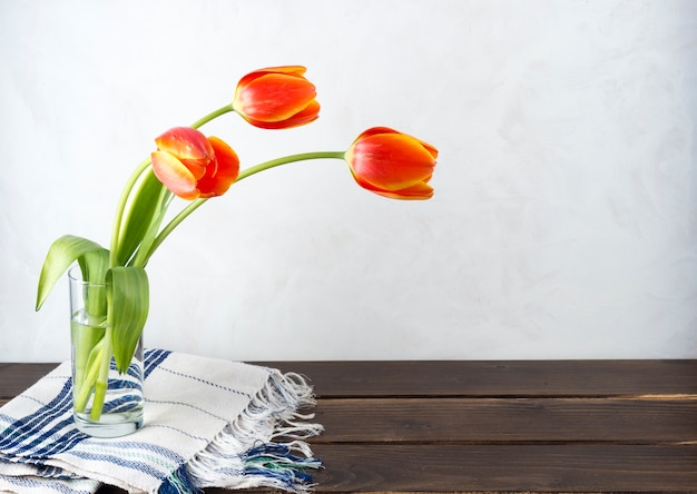 Red tulips in glass vase on table Free Photo