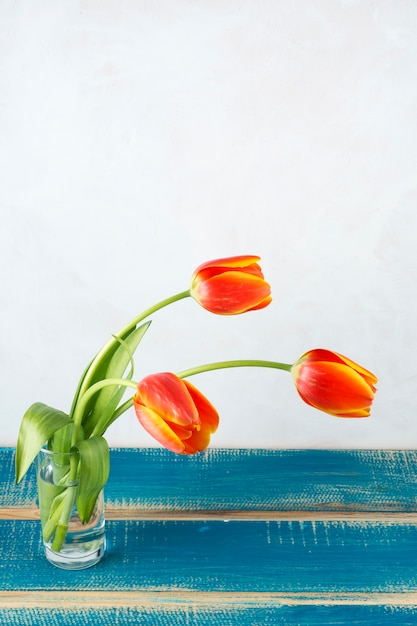 Red tulips in glass vase on wooden table Free Photo