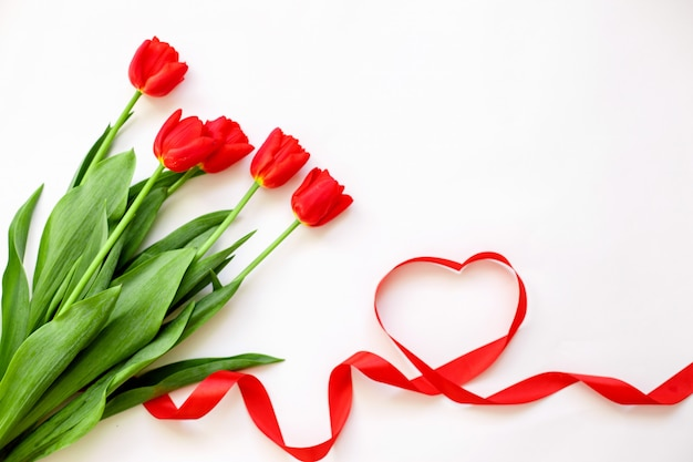 Red tulips and a ribbon heart . valentine's day, mother's day, wedding, women's day-concept Premium Photo