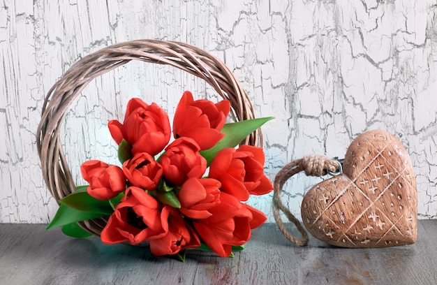 Red tulips and wooden heart on white cracked background Premium Photo