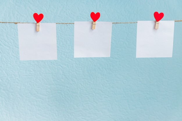 Red valentine's love hearts pins hanging on natural cord against blue background. mock up concept for your text Premium Photo