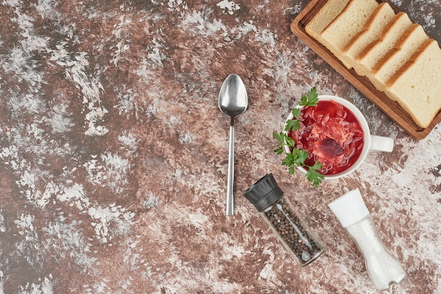 ハーブと白いカップの赤い野菜スープ。 無料写真