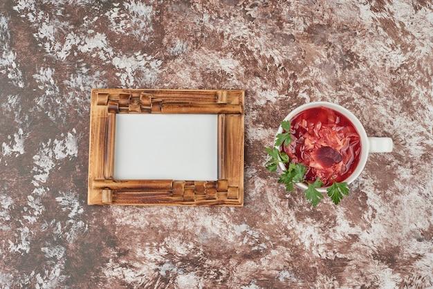 Zuppa di verdure rossa in una tazza bianca con erbe aromatiche. Foto Gratuite