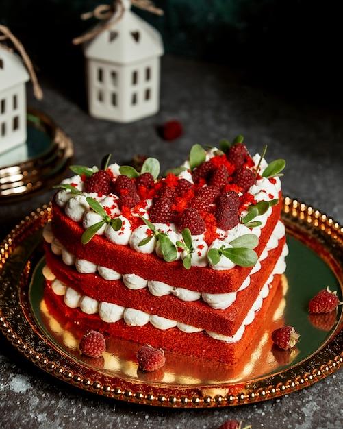 Красный бархатный торт в форме сердца, украшенный малиной и листьями мяты Бесплатные Фотографии