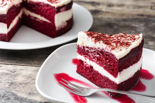 木製のテーブルに赤いベルベットケーキのスライス Premium写真