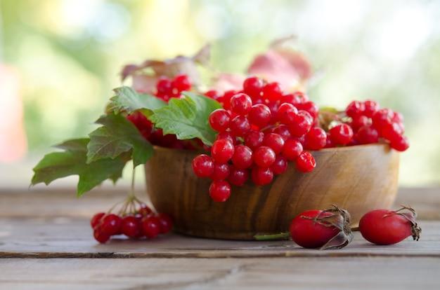 2つのローズヒップとテーブルの上の木製のボウルに赤いガマズミ属の果実 Premium写真